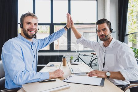 Photo for Young call center operators in headsets giving high five and smiling at camera while working together in office - Royalty Free Image