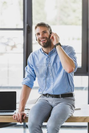 handsome smiling young call center operator in headset sitting on table in office
