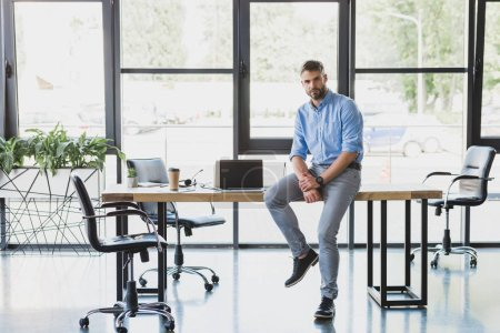 Photo for Full length view of handsome young businessman sitting on table and looking at camera in office - Royalty Free Image