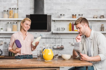 boyfriend reading newspaper and girlfriend holding container with cornflakes and milk in kitchen