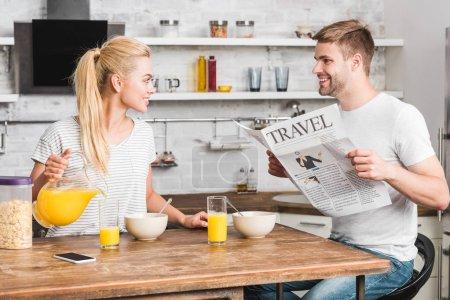 Photo pour Petite amie verser du jus dans le verre et petit ami lecture journal pendant le petit déjeuner dans la cuisine - image libre de droit