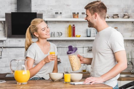 Photo for Boyfriend holding container of cornflakes and looking at girlfriend during breakfast in kitchen - Royalty Free Image