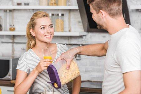 Photo pour Cornflakes battante copain dans la plaque pendant le petit déjeuner dans la cuisine, petite amie tenant le verre de jus - image libre de droit
