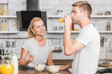 boyfriend drinking orange juice during breakfast in kitchen