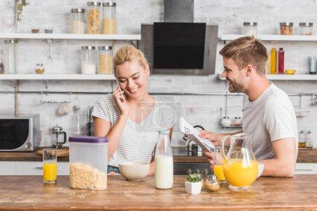 girlfriend talking by smartphone during breakfast in kitchen