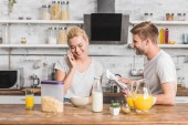 girlfriend talking by smartphone during breakfast in kitchen