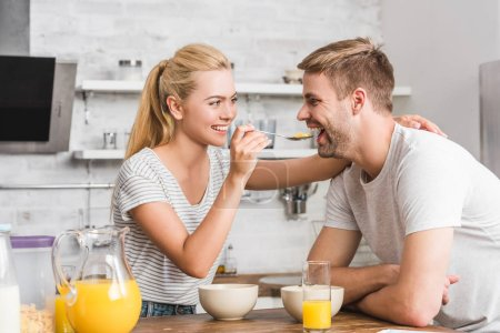 smiling girlfriend feeding boyfriend with cornflakes in kitchen