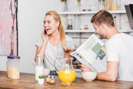 Photo pour Petite amie parler par smartphone pendant le petit déjeuner dans la cuisine, petit ami lecture journal - image libre de droit