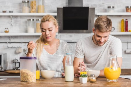 Photo for Couple having cornflakes with milk on breakfast in kitchen - Royalty Free Image