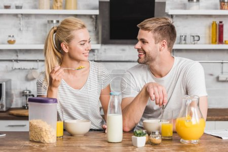 Photo for Smiling couple having breakfast and looking at each other in kitchen - Royalty Free Image