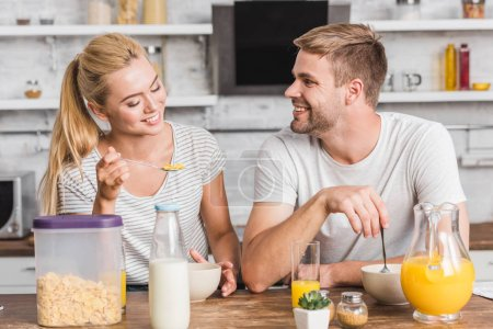 Photo for Smiling couple eating cornflakes with milk on breakfast in kitchen - Royalty Free Image