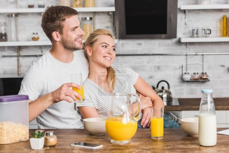 Photo for Happy boyfriend hugging girlfriend during breakfast and holding glass of juice in kitchen - Royalty Free Image