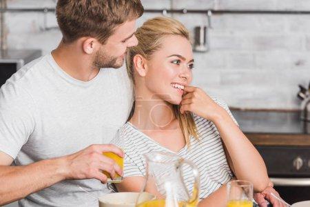 Photo for Happy boyfriend hugging girlfriend during breakfast in kitchen - Royalty Free Image