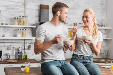 Photo for Cheerful couple holding plates and spoons with corn flakes and looking at each other in kitchen - Royalty Free Image