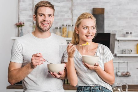 happy couple holding plates and spoons with corn flakes in kitchen