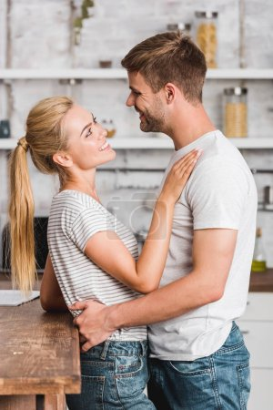 side view of happy heterosexual couple hugging in kitchen and leaning on kitchen counter
