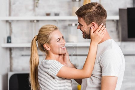 side view of smiling couple hugging in kitchen and touching faces