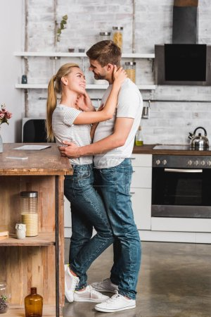 Photo for Side view of couple hugging in kitchen and leaning on kitchen counter - Royalty Free Image