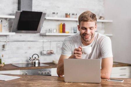 Photo for Handsome smiling man holding cup of coffee and looking at laptop in kitchen - Royalty Free Image