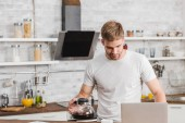 handsome man holding coffee pot and looking at laptop in kitchen
