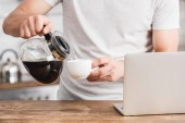 cropped image of man pouring coffee into cup near laptop in kitchen