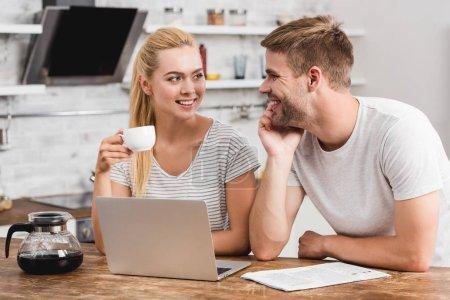 Photo pour Couple travaillant ensemble avec ordinateur portable le matin et se regardant - image libre de droit