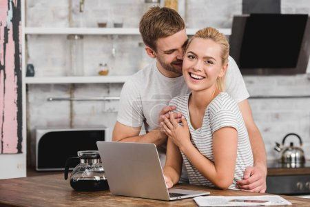 boyfriend hugging laughing girlfriend in kitchen while she working with laptop