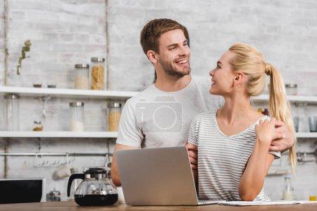 happy boyfriend hugging girlfriend in kitchen while she working with laptop