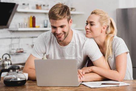 cheerful girlfriend hugging boyfriend in kitchen and he using laptop