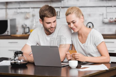 smiling young couple holding business card and using laptop together at kitchen table