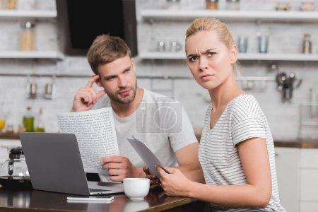 Photo for Frowning young woman holding papers and looking at camera while using laptop with boyfriend at home - Royalty Free Image