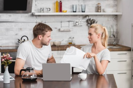 young couple holding papers and using laptop while sitting at kitchen table and looking at each other