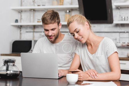 smiling young couple with credit card using laptop at home