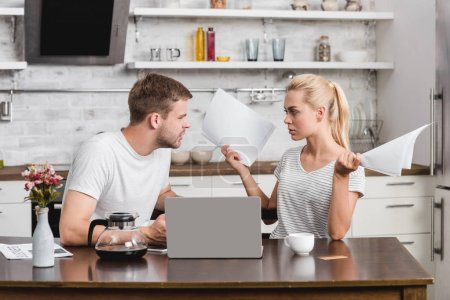 emotional young couple arguing and looking at each other while using laptop and holding papers at home