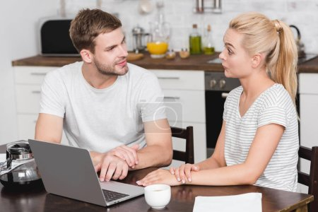 Photo for Beautiful young couple using laptop and looking at each other in kitchen - Royalty Free Image