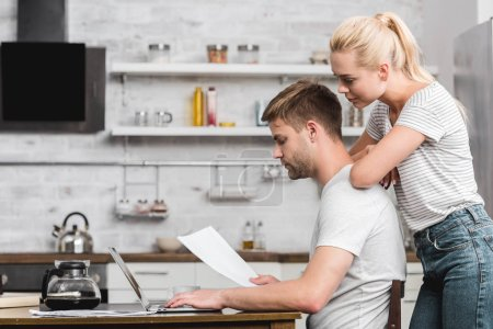 Photo for Side view of young couple looking at paper sheet and using laptop together at home - Royalty Free Image