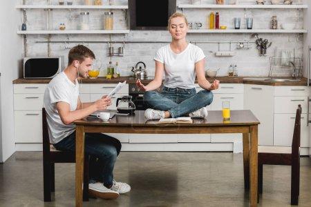 Foto de Hombre joven en auriculares leyendo el periódico mientras bella novia meditando sobre la mesa de la cocina - Imagen libre de derechos