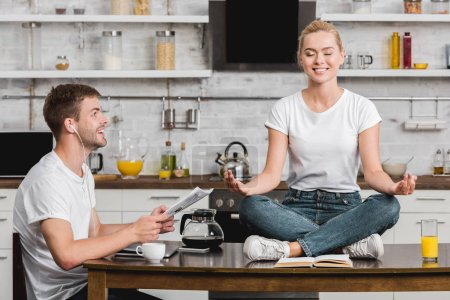 smiling young man reading newspaper and looking at happy girlfriend meditating on kitchen table