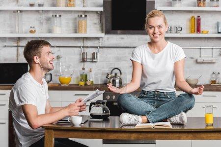 Photo pour Jeune homme souriant écouteurs lire le journal et en regardant bonne copine en méditant sur la table de la cuisine - image libre de droit
