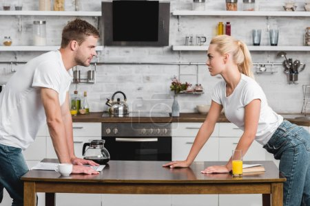 side view of passionate young couple looking at each other in kitchen