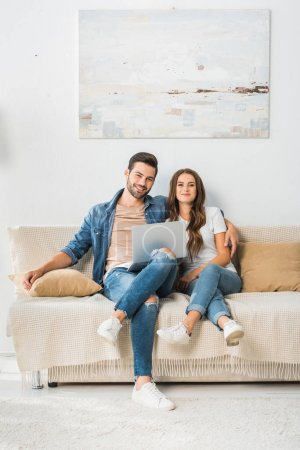 Photo pour Souriante jeune couple assis sur le canapé avec ordinateur portable à la maison - image libre de droit