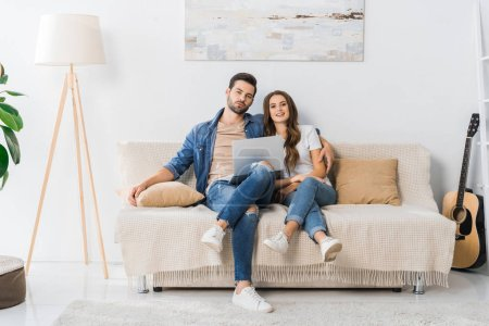 young couple with laptop sitting on couch at home