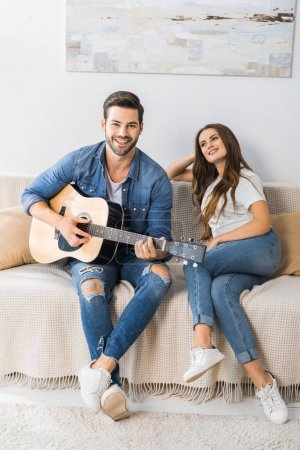 Photo for Smiling young man playing on acoustic guitar while his girlfriend sitting near on couch at home - Royalty Free Image