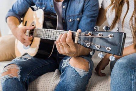 Photo pour Vue partielle de l'homme jouant sur la guitare acoustique tandis que sa petite amie assis près sur le canapé à la maison - image libre de droit