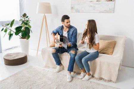 Photo pour Jeune bel homme jouant sur la guitare acoustique tandis que sa petite amie danse près sur le canapé à la maison - image libre de droit