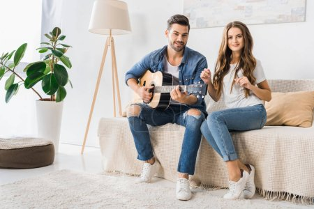 Photo for Young smiling couple sitting on couch with acoustic guitar and looking at camera at home - Royalty Free Image