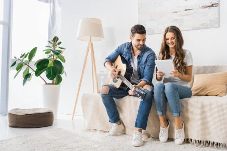 smiling couple tuning acoustic guitar with digital tablet on sofa at home