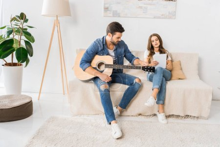 Photo for Young couple tuning acoustic guitar with digital tablet on sofa at home - Royalty Free Image