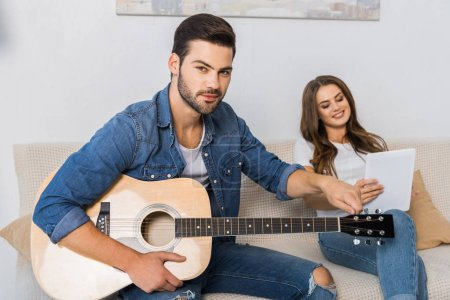 Photo for Confident man tuning guitar and looking at camera while his girlfriend sitting near with digital tablet on sofa at home - Royalty Free Image