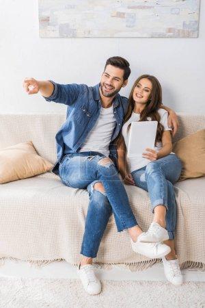 Photo pour Sourire jeune homme pointant du doigt à la petite amie avec tablette numérique sur le canapé à la maison - image libre de droit